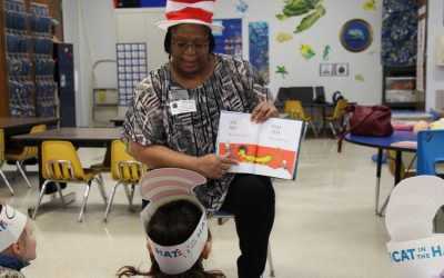 Employee from Navy Army Credit Union reads a Dr Seuss book to ECC pre-k students