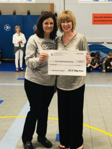 """ECC Principal Amy Seeds presents a $1,000 check to Olsen Elementary School in Port Aransas ISD. The money was raised through the """"Lil' Helping Hornets"""" community service project"""
