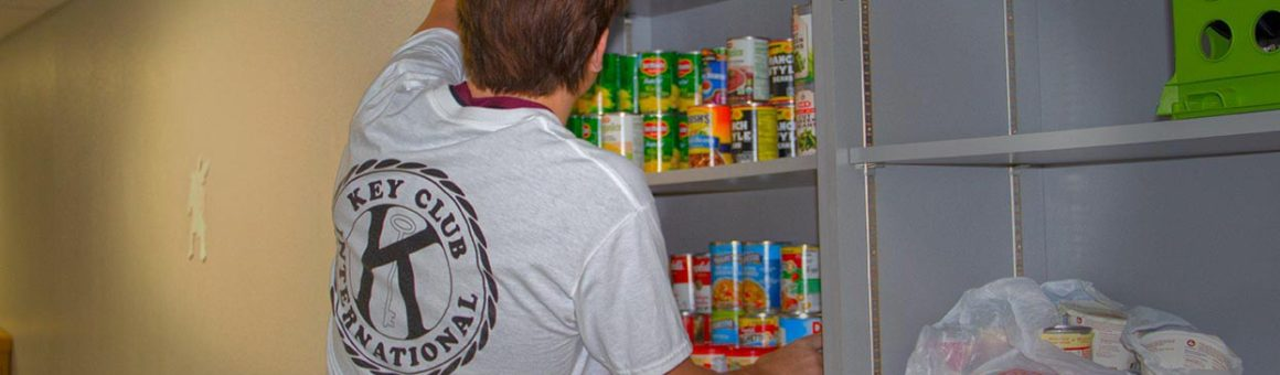 student stocking key clubs food pantry image
