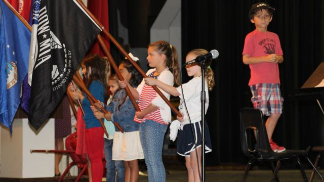 picture of students holding flags at Primary's Veterans Day Ceremony