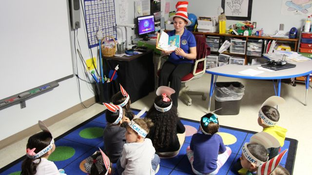 image Navy Army Credit Union representative reads to students at the ECC in celebration of Dr Seuss Day