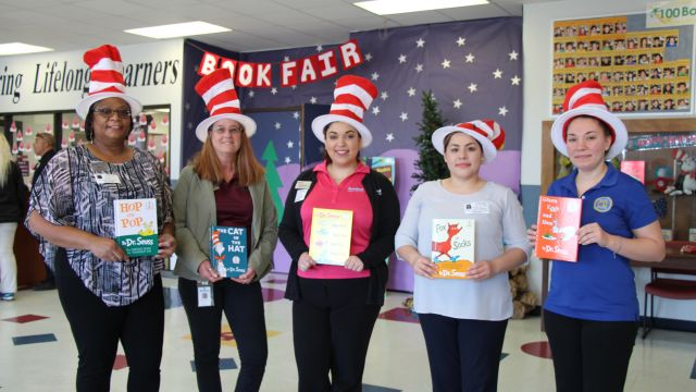 image employees of Navy Army Credit Union show off the Dr Seuss book they read